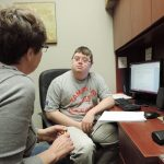 Image is of a man at his work desk talking with his female support worker.