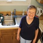 Image is of a woman smiling in her kitchen.
