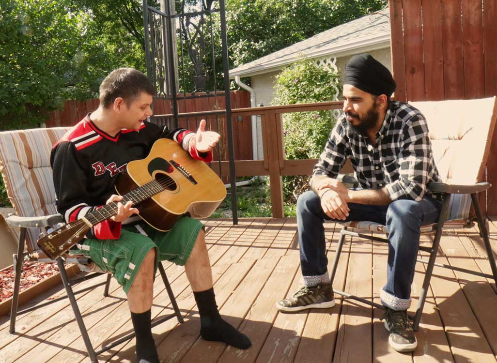 Image is of a man playing a guitar outside with his male support worker.